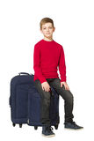 Boy sitting on travel bags isolated on white Royalty Free Stock Photos