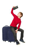 Boy sitting on travel bags looking insight empty wallet isolated Royalty Free Stock Photo