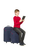 Boy sitting on travel bags with tablet pc isolated on white Stock Image