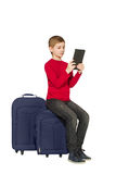 Boy sitting on travel bags using tablet isolated on white Royalty Free Stock Photography