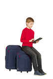 Boy sitting on travel bags using tablet pc on white Stock Photo