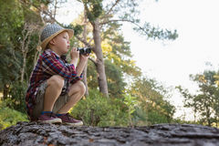 Boy sitting on the tree trunk with binoculars. In the forest Royalty Free Stock Photo