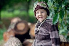 Boy, sitting on a tree trunks Stock Photos