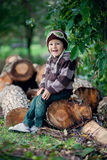 Boy, sitting on a tree trunks Stock Photos