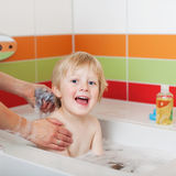 Boy Sitting In Tub While Mother Bathing Him Royalty Free Stock Image