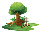 A boy sitting under the big tree Stock Photo