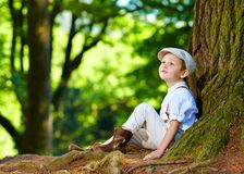 Boy sitting under an old tree, in the forest Stock Photo