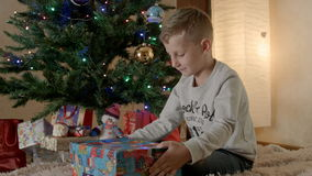 Boy sitting under the tree and unpacking Christmas gift stock footage