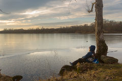 Boy sitting by the water in the early spring. Royalty Free Stock Image