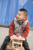 Boy sitting on wheelbarrow Royalty Free Stock Photography