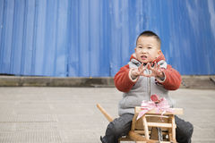 Boy sitting on wheelbarrow Royalty Free Stock Image