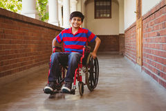 Boy sitting in wheelchair in school corridor