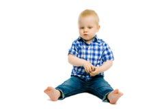 Boy sitting on a white floor Stock Photos