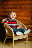 Boy sitting in wicker chair Stock Photo