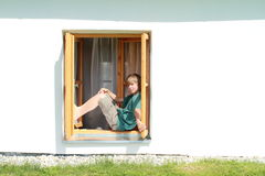 Boy sitting on the window Stock Image