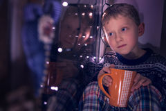 Boy sitting on window decorated for Christmas Eve Royalty Free Stock Photography