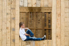 Boy sitting in the window opening Stock Photography