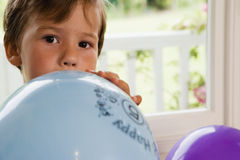 Boy (4-6) sitting on window seat at home, blowing air into blue party balloon, close-up, front view, portrait Stock Photo