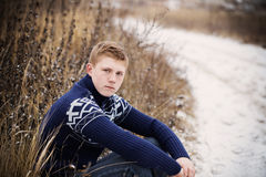 boy sitting at winter road Royalty Free Stock Photos
