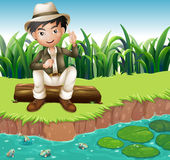 A boy sitting on a wood at the riverbank Royalty Free Stock Images