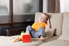 Boy sitting with wooden building toys at home Royalty Free Stock Photos