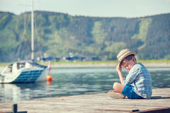 Boy sitting on wooden pier Stock Photos