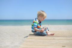 Boy sitting on a wooden walkway on the beach Stock Photo