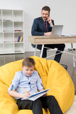 Boy sitting on yellow pillow and drawing while his father businessman royalty free stock photography