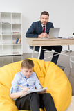 Boy sitting on yellow pillow and drawing while his father businessman stock image