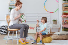 Boy practicing correct pronunciation. Boy sitting on a yellow pouf practicing correct pronunciation during a lesson with speech therapist Stock Photo