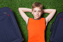 Boy and siutcases th lying on green grass close up Stock Photos