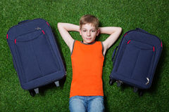 Boy with siutcases th lying on green grass royalty free stock photos