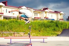 A boy in a skate park doing a trick on a skateboard. Boy skateboarder in a skate park doing an ollie trick on a skateboard against a sky and thunderclouds Royalty Free Stock Photos