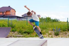 A boy in a skate park doing a trick on a skateboard. Boy skateboarder in a skate park doing an ollie trick on a skateboard against a sky and thunderclouds Royalty Free Stock Photography