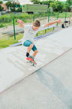 A boy in a skate park doing a trick on a skateboard Royalty Free Stock Photography