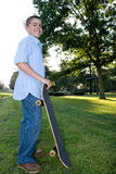 Boy with Skateboard. A boy in his early teens happily standing with his skateboard Stock Image