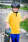 Boy with skateboard. Boy wearing a helmet outdoors with his skateboard Royalty Free Stock Photos