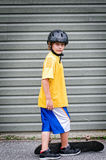 Boy with skateboard. Young boy skateboarding wearing helmet Royalty Free Stock Images