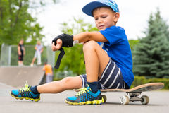 Boy on Skateboard Adjusting Elbow Pad in Park. Full Length of Young Boy Looking Upset Down at Arm While Adjusting Elbow Pad and Sitting on Skateboard in Skate Stock Photography
