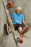 Boy (11-13) with skateboard against wall, smiling, portrait Royalty Free Stock Photography