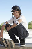 Boy With Skateboard Crouching In Skate Park Stock Image