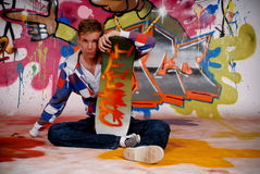 Boy skateboard, graffiti wall. Handsome teenager boy with his skateboard in front of graffiti wall, urban setting.  Studio shoot Royalty Free Stock Photography