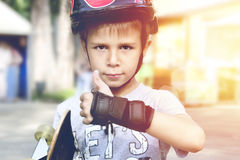 Boy with skateboard showing thumbs up stock photo