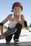 Boy With Skateboard Squatting In Skate Park Royalty Free Stock Images