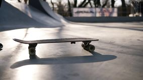 Boy with skateboard is about to start his ride. Teen skater in the skate city park. Close up of feet of skateboarder on stock footage
