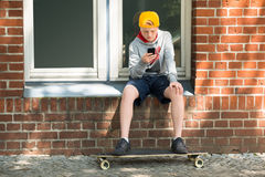 Boy With Skateboard Using At His Mobile Phone Stock Photography