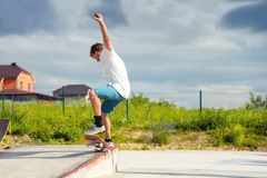 A boy in a skate park doing a trick on a skateboard. Boy skateboarder in a skate park doing an ollie trick on a skateboard against a sky and thunderclouds Royalty Free Stock Image
