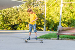 Boy skateboarding on natural background Royalty Free Stock Images