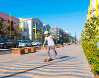 Boy skateboarding In Santa Monica. Two skateboard buddies heading to the beach in Santa Monica, California in front of the world famous Santa Monica Pier. Palm Royalty Free Stock Images