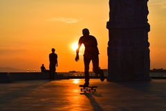A boy skateboarding at sunset, silhouette. Stock Images